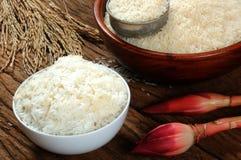Gekookte rijst, ongekookte rijst en padie op houten lijst Stock Afbeeldingen