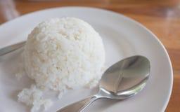 Gekookte rijstvork en lepel in witte schotel Stock Afbeelding