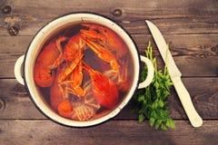 Gekookte rivierkreeften in een pan, greens van peterselie en een mes Royalty-vrije Stock Foto