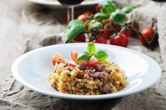 Gekookte sardinain deegwarenfregola met tomaat en worst stock foto's