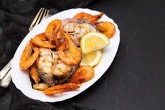 Gekookte vissen met garnalen en citroen op witte schotel Stock Foto