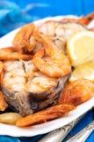 Gekookte vissen met garnalen en citroen op witte schotel Royalty-vrije Stock Afbeeldingen