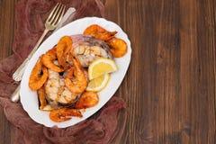Gekookte vissen met garnalen en citroen op witte schotel Royalty-vrije Stock Foto's