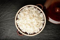 Gekookte witte rijst in ceramische pot op houten achtergrond Stock Foto