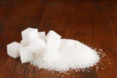 Gekorrelde witte suiker in een stapel met sommige kubussen op een bruine houten achtergrond stock afbeelding