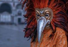 Gekostumeerd Carnaval -Carnaval-goer met rood bevederd masker die zich in St Teken` s Vierkant tijdens Venetië Carnaval Carnivale stock afbeelding