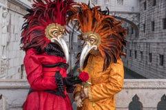Gekostumeerde Carnaval-goers met rood bevederd masker die zich binnen door de Brug van Sighs tijdens Venetië Carnaval Carnivale D royalty-vrije stock afbeeldingen