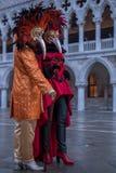 Gekostumeerde Carnaval-goers met rood bevederd masker die zich in St Teken` s Vierkant tijdens Venetië Carnaval Carnivale Di Vene royalty-vrije stock foto's