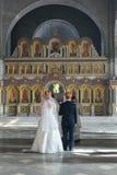Gekrönter Braut- und Bräutigamstand in der Kirche hinter den Priestern Stockbilder
