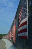 Gekrümmte Linie von amerikanischen Flaggen auf Sonnenseite des Landstraßenüberführungszauns Stockbild