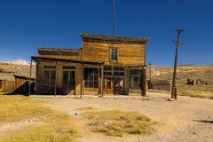 Gekrümmtes verlassenes Westsaalgebäude und -Shop in Bodie Ghost Town Stockfotografie