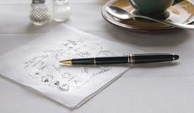 Gekrabbel op Servet bij Lijst met Pen Royalty-vrije Stock Afbeeldingen
