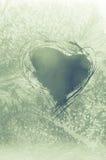 Gekrast hart op ijzig venster stock fotografie