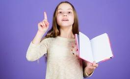 Gekregen nieuwe informatie Meisje dat open boek houdt en vinger houdt die voor essentiële informatie wordt opgeheven Klein kind m royalty-vrije stock foto's