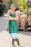 Gekreuzte Arme der Garten-Center-Arbeitnehmerin Stellung Stockbilder