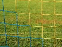 Gekreuzte Fußballnetze, Fußballfußball im Zielnetz mit Plastikgras auf Fußballspielplatz Stockbild