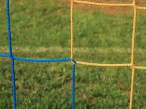 Gekreuzte Fußballnetze, Fußballfußball im Zielnetz mit Plastikgras auf Fußballspielplatz Lizenzfreies Stockbild