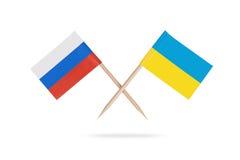Gekreuzte Miniflaggen Ukraine und Russland Stockbilder