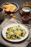 Gekrochene Eier mit Spinat, Tasse Tee auf dunkelbraunem Hintergrund vertikal Frühstück mit Pan-gebratenem Omelett, Seitenansicht, stockbild