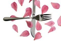 Gekruist zilveren vork en mes met roze bloemblaadjes Royalty-vrije Stock Fotografie