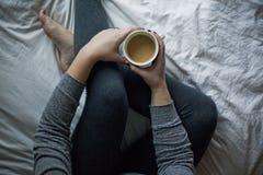 Gekruiste beenkoffie in bed Royalty-vrije Stock Foto's