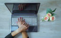 Gekruiste handen van vrouw op een computer royalty-vrije stock foto's
