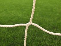 Gekruiste voetbalnetten, voetbalvoetbal in doel netto met plastic gras op voetbalspeelplaats Royalty-vrije Stock Afbeelding