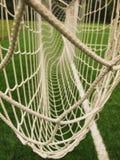 Gekruiste voetbalnetten, voetbalvoetbal in doel netto met plastic gras op voetbalspeelplaats Stock Fotografie