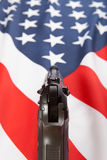 Gekräuselte Flagge mit Faustfeuerwaffe über ihr Reihe - die Vereinigten Staaten von Amerika Stockbild