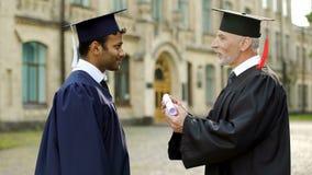 Gekwalificeerde professor die diploma geven aan mengen-ras mannelijke student die hem gelukwensen royalty-vrije stock foto