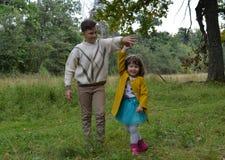 Gelächterspaßschwesterbruder-Vatiliebe außerhalb des Waldjungen lächelnder Wegnatur draußen f des jungen des Sommers Tochterpaarb Stockfoto