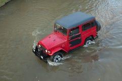 Geländeauto in einem Fluss Stockbild