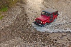 Geländeautodurchläufe durch den Fluss Lizenzfreies Stockbild