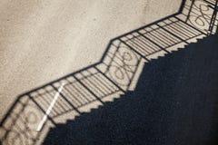 Geländerschattenmuster auf einem leeren Straßenasphalt Lizenzfreies Stockfoto