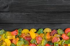 Gelé- och marmeladgodisar på en träbakgrund fotografering för bildbyråer