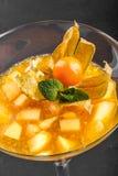 Gelée de fruit de la mangue et de la pêche décorées de la menthe et du physalis dans un verre sur le fond en pierre foncé images stock
