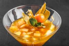 Gelée de fruit de la mangue et de la pêche décorées de la menthe et du physalis dans un verre sur le fond en pierre foncé photo stock