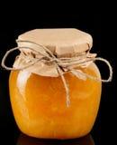 Gelée orange dans le pot en verre d'isolement sur le noir image stock