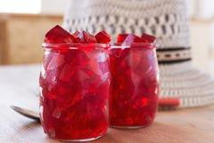 Gelée rouge, coupe en matrices, à l'intérieur de deux verres de verre Photographie stock libre de droits