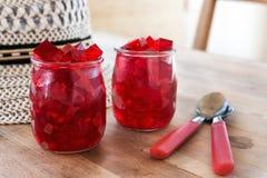 Gelée rouge, coupe en matrices, à l'intérieur de deux verres de verre Photos libres de droits