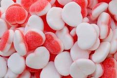 Gelésockergodisar Röd och vit bakgrund av hjärtor royaltyfria bilder