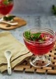 Gel? med jordgubbar i ett exponeringsglas p? ett tr?br?de, mot en bakgrund av betong fotografering för bildbyråer