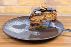 Gelaagd chocoladebiscuitgebak met vork op bruine schotelclose-up royalty-vrije stock fotografie