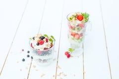 Gelaagd dessert met framboos, aardbei, zwarte bes en kiwi, room en koekjes in glazen royalty-vrije stock fotografie