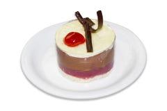 Gelaagd dessert op een witte plaat op een lichte achtergrond stock fotografie