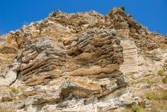 Gelaagd die rotsgezicht op een steengroeve wordt gezien stock fotografie
