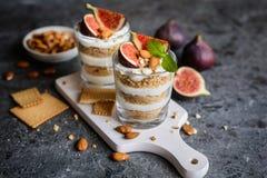Gelaagd mascarponedessert met verpletterde vanillekoekjes, fig. en amandelen stock foto's