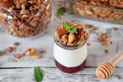 Gelaagd ontbijt met granola, yoghurt en jam in een glaskruik royalty-vrije stock fotografie