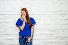 Gelaatsuitdrukkingen van Jonge Roodharigevrouw op Bakstenen muur Stock Foto's