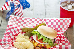 Geladen cheeseburger bij als thema gehad patriottisch cookout Royalty-vrije Stock Afbeelding